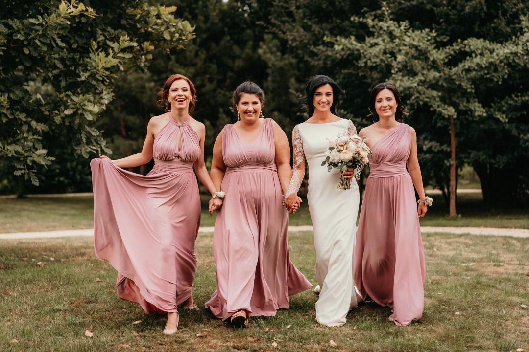 Nevesta a tri družičky s jemne ružovými šatami , kráčajú lúkou.
