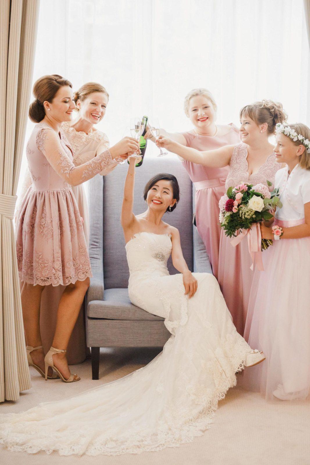 Nevesta sedí na púdrovom modrom kresle a pripíja si šampanským s piatimi družičkami. Družičkovské šaty sú v púdrovej ružovej farbe.