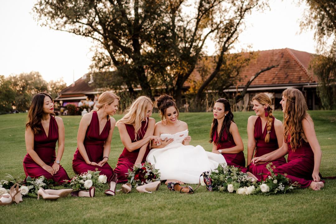 nevesta so šiestimi družičkami v bordových šatách sedia na dvore v tráve.