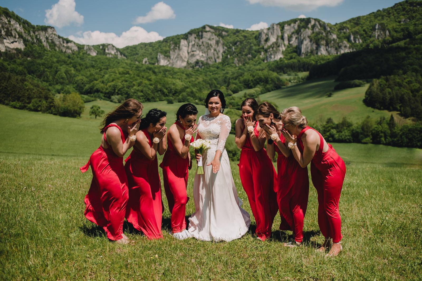 nevesta so šiestimi družičkami v červených šatách na lúke. Družičky obdivujú zásnubný prsteň.