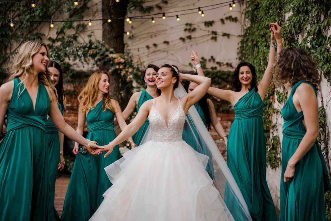 Nevesta so siedmimi družičkami v smaragdových šatách tancujú na parkete ozdobeným svetielkami.