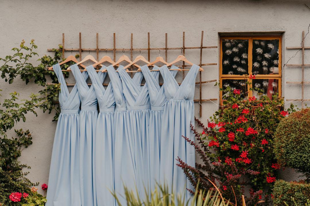 Družičkovské šaty v púdrovej modrej farbe, zavesené na drevených vešiakoch v záhrade.