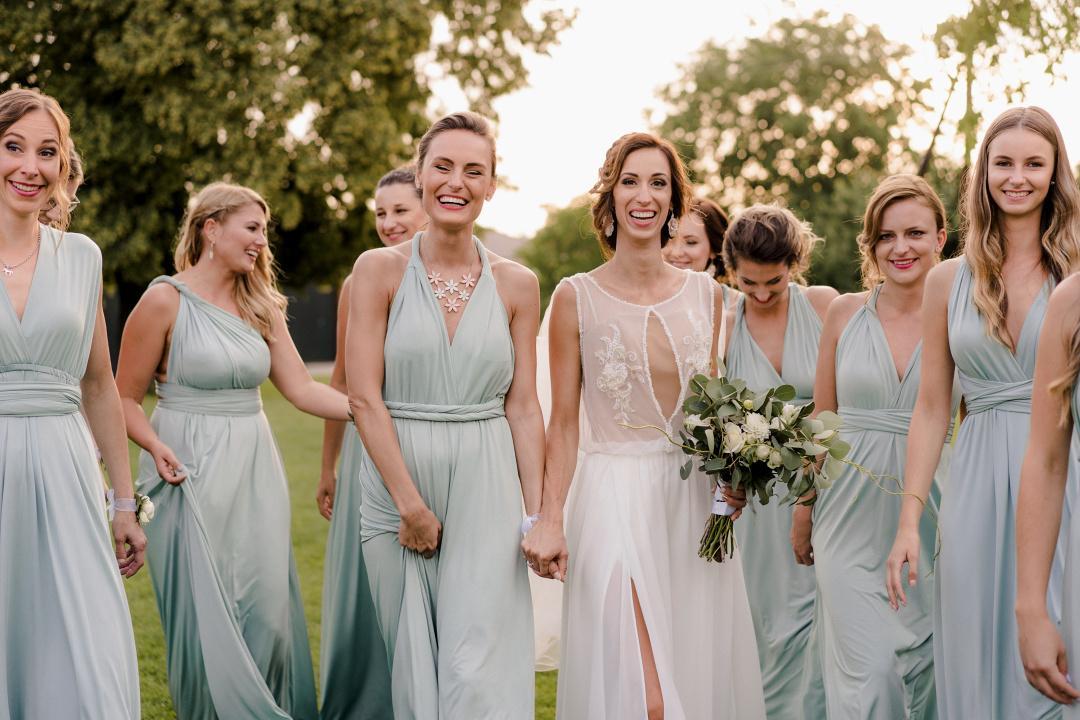 Nevesta s deviatimi družičkami v púdrovo modrých šatách kráčajú lúkou. Nevesta drží svadobnú kyticu a všetky sa smejú.