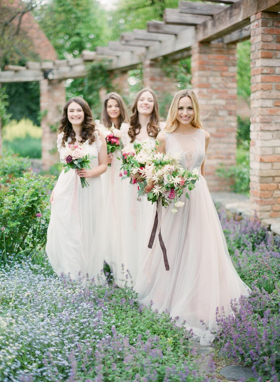 Štyri družičky, ktoré držia svadobné kytice v zeleno-bielo-bordových odtieňoch.