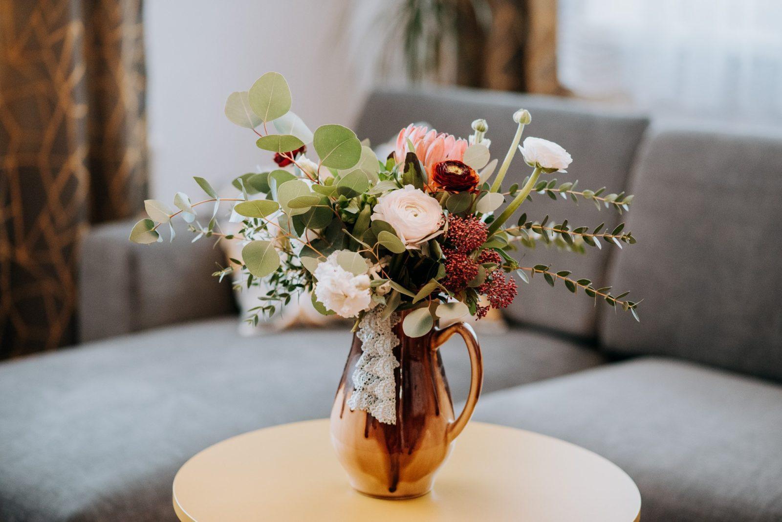 Svadobná kytica v medenej váze uviazaná z bielych rununculusov, ružových ruží, bordových pivonieka zelene.