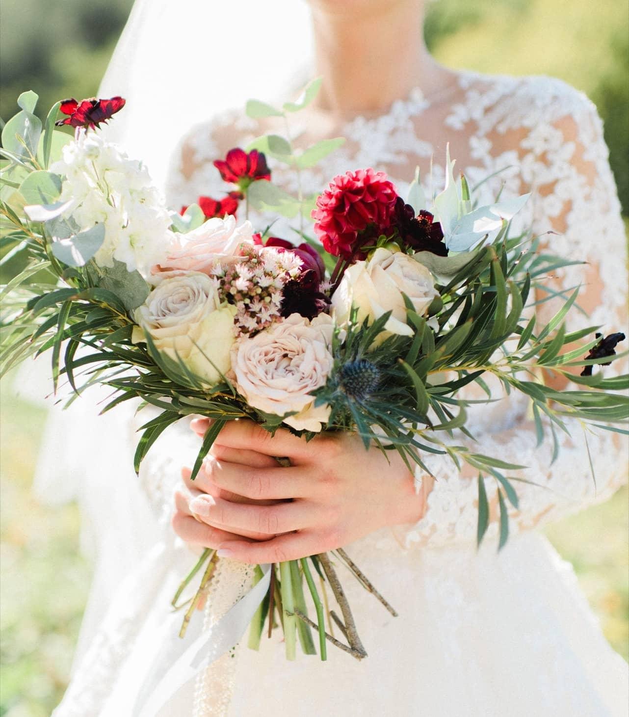 Nevesta drží svadobnú kyticu s ružovými ružami, bordovými dáliami a zeleňou.