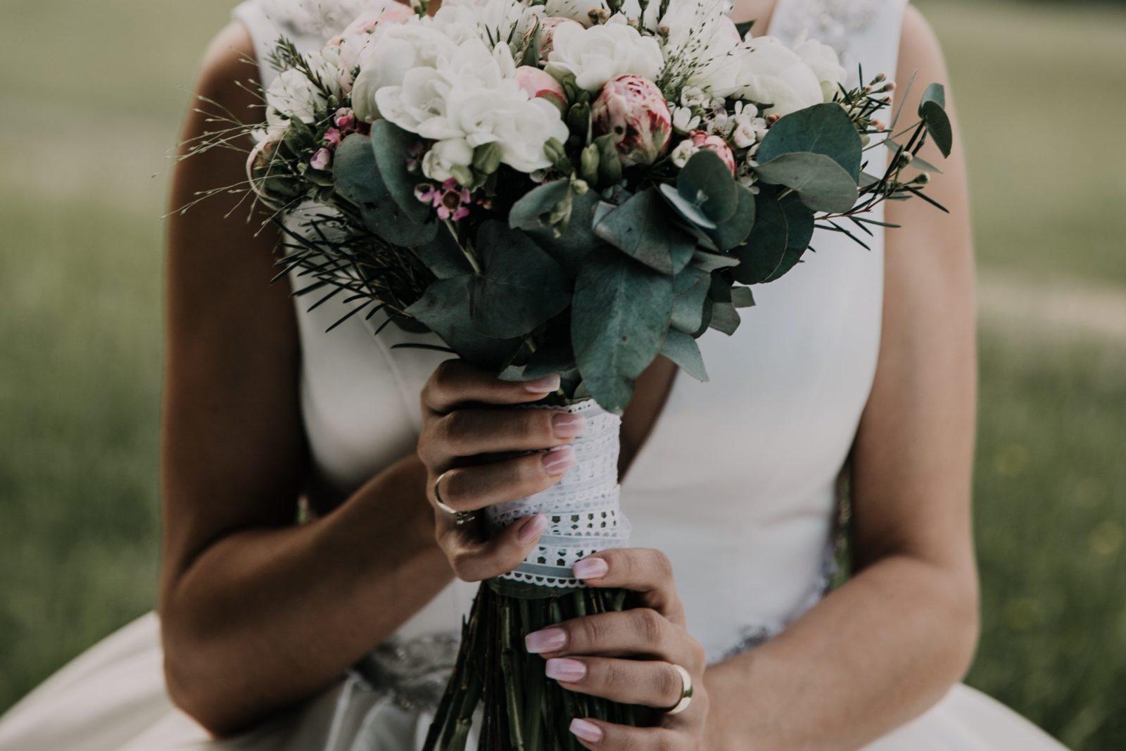 Svadobná kytica v nevestiných rukách zviazaná bielou stuhou.