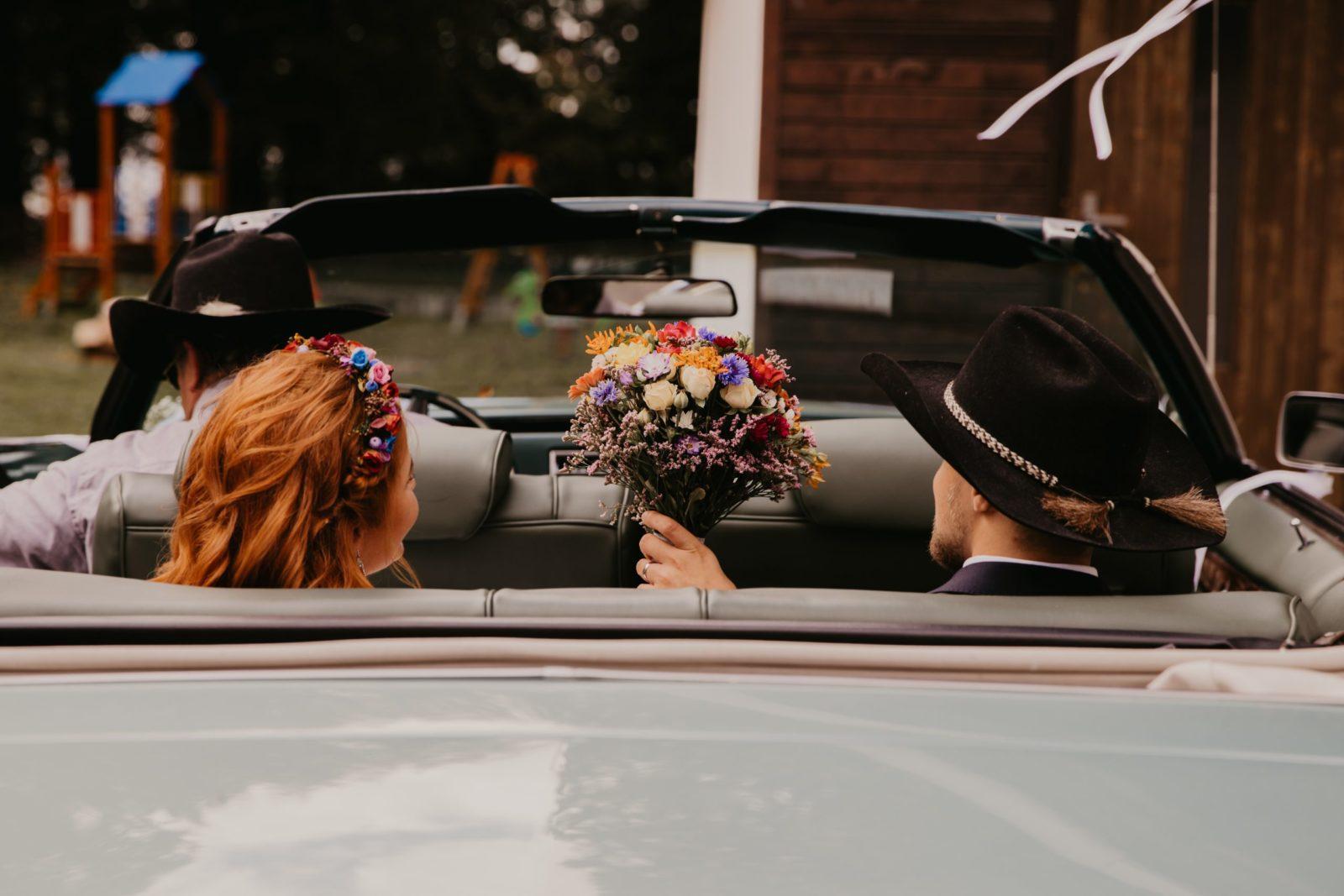 Novomanželia v kabriolete držia nad hlavami svadobnú kyticu.