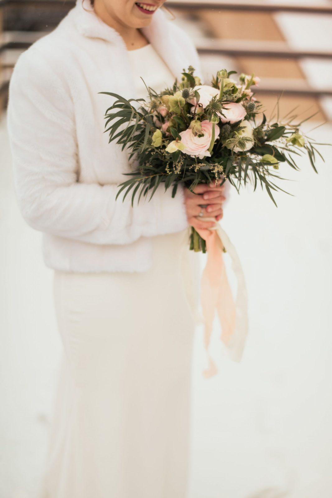 Svadobná kytica v rukách nevesty, okolo je nasnežené.