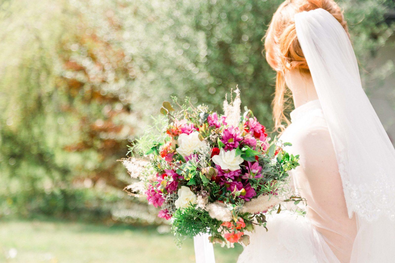 Nevesta so závojom drží kyticu z lúčnych kvetov.