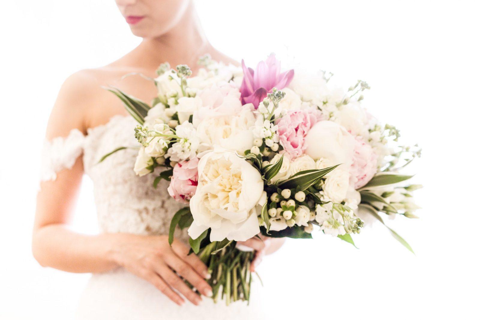 Nevesta drží kyticu uviazanú v bielo,ružových a zelených farbách.