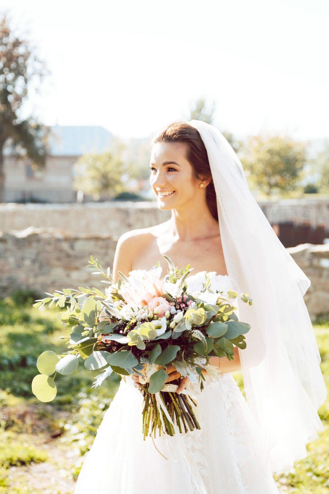 Nevesta so závojom drží kyticu z farebných kvetov.