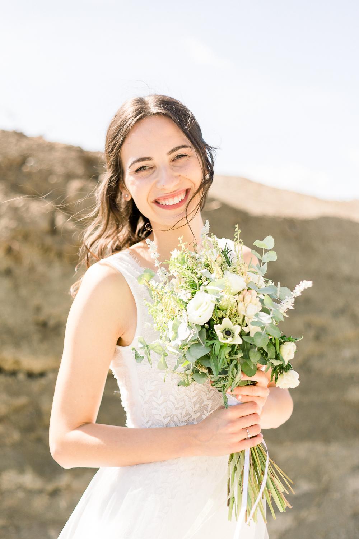 Usmievajúca sa nevesta so svadobnou kyticou v zeleno-bielych farbách.