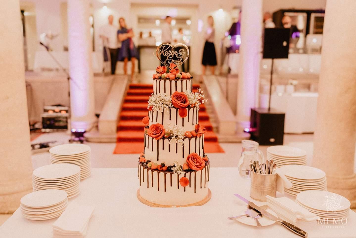Svadobná torta. Štvorposchodová biela s čokoládou ozdobená oranžovými kvetmi.
