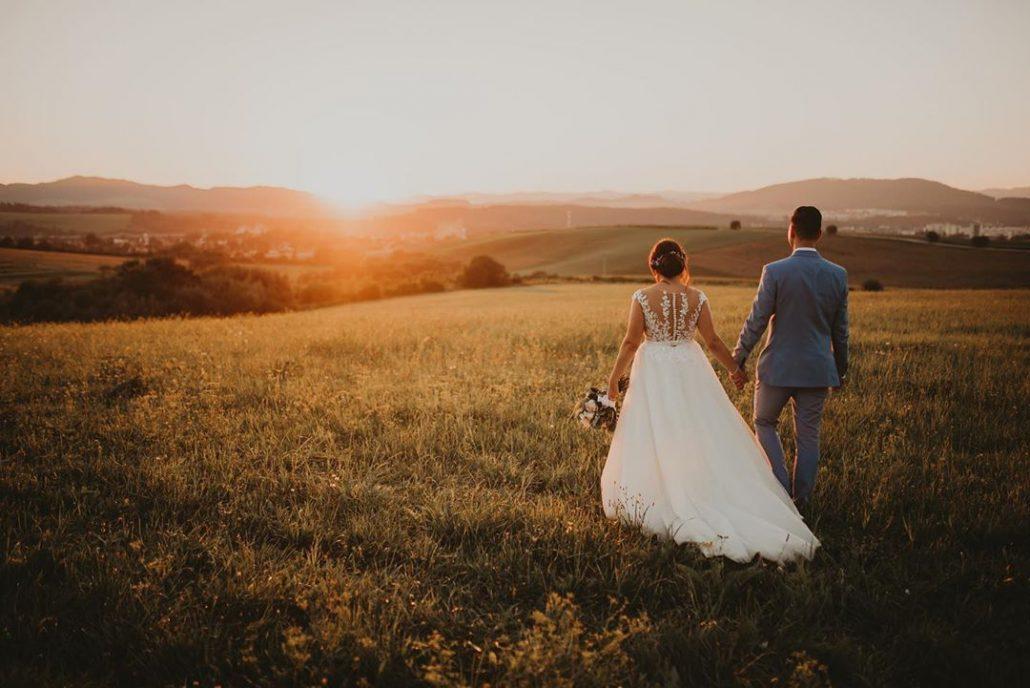 Nevesta a ženích si užívajú západ slnka na svadobnom fotení.