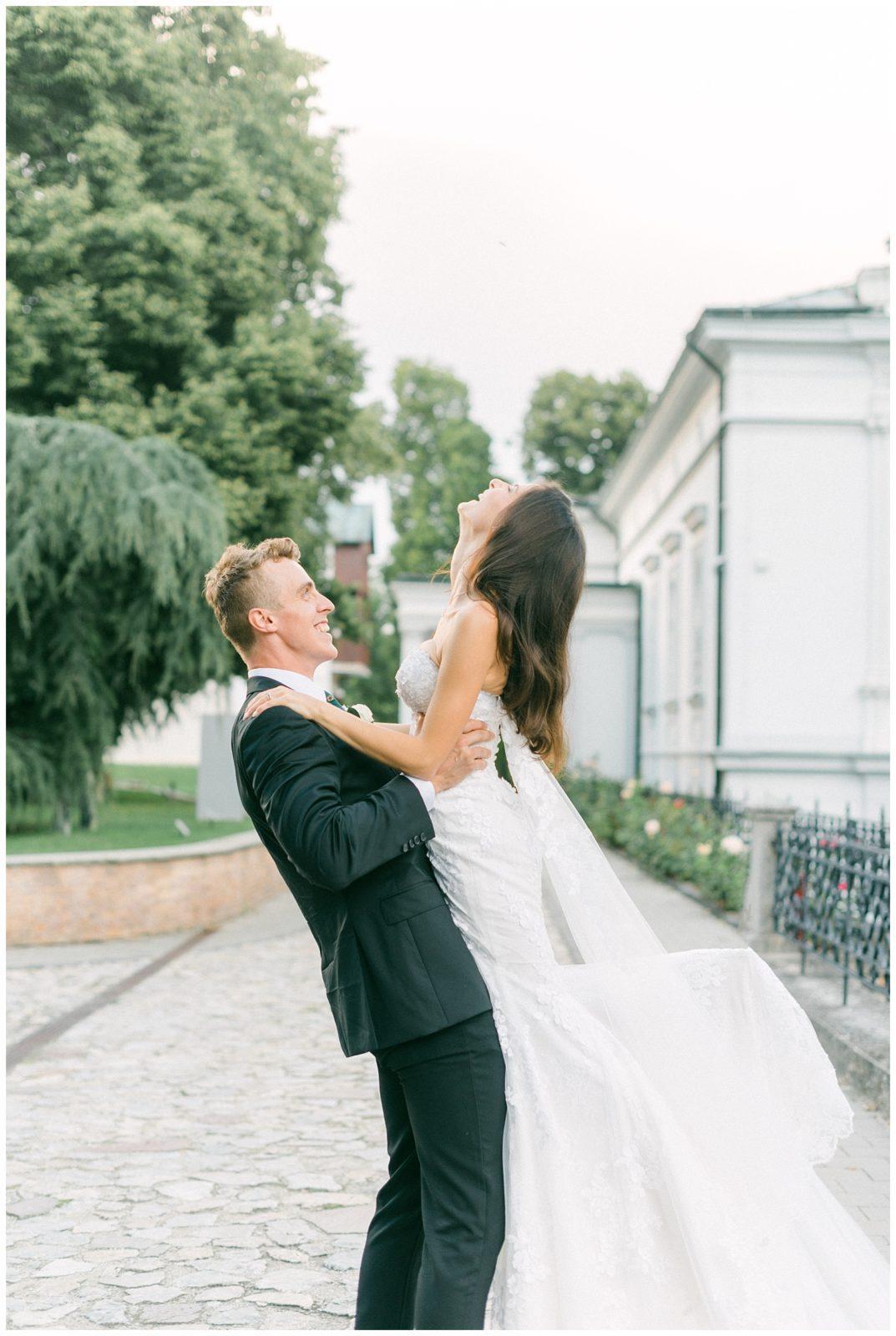 Zaľúbený novomanželia fotení v exteriéri.
