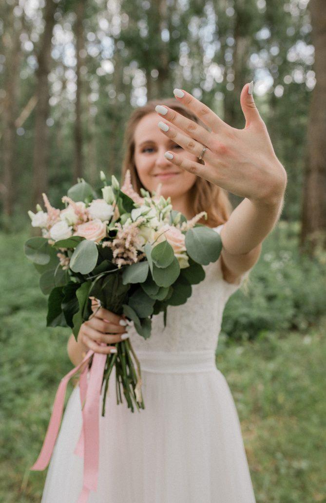 Nevesta ukazujúca obrúčku a svadobnú kyticu.