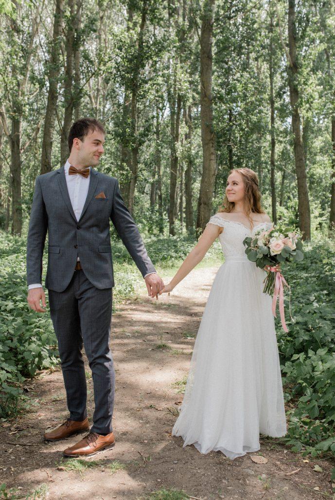 Fotografia novomanželov na prechádzke cez les.