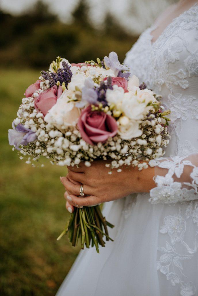 Svadobná kytica v nevestiných rukách.