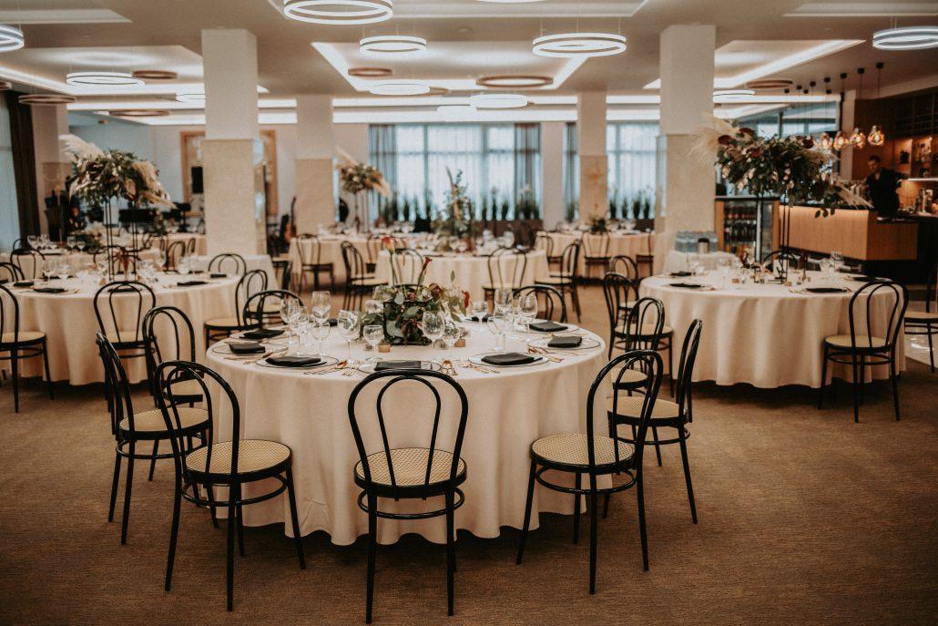 Svadobná výzdoba okrúhlych stolov v kombinácii s čiernymi stoličkami.