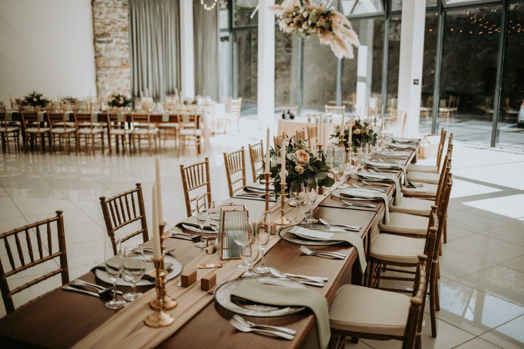 Kombinácia okrúhlych a podlhovastých stolov vo svadobnej výzdobe.