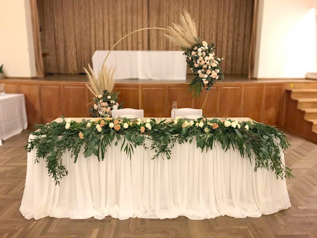Hlavný stôl novomanželov dekorovaný v Boho štýle od svadobnej agentúry Endless. Po dĺžke celého stola sa tiahne krásny zelený aranžmán zo zelene. Za stolom je nadekorovaná kruhová slavobrána.