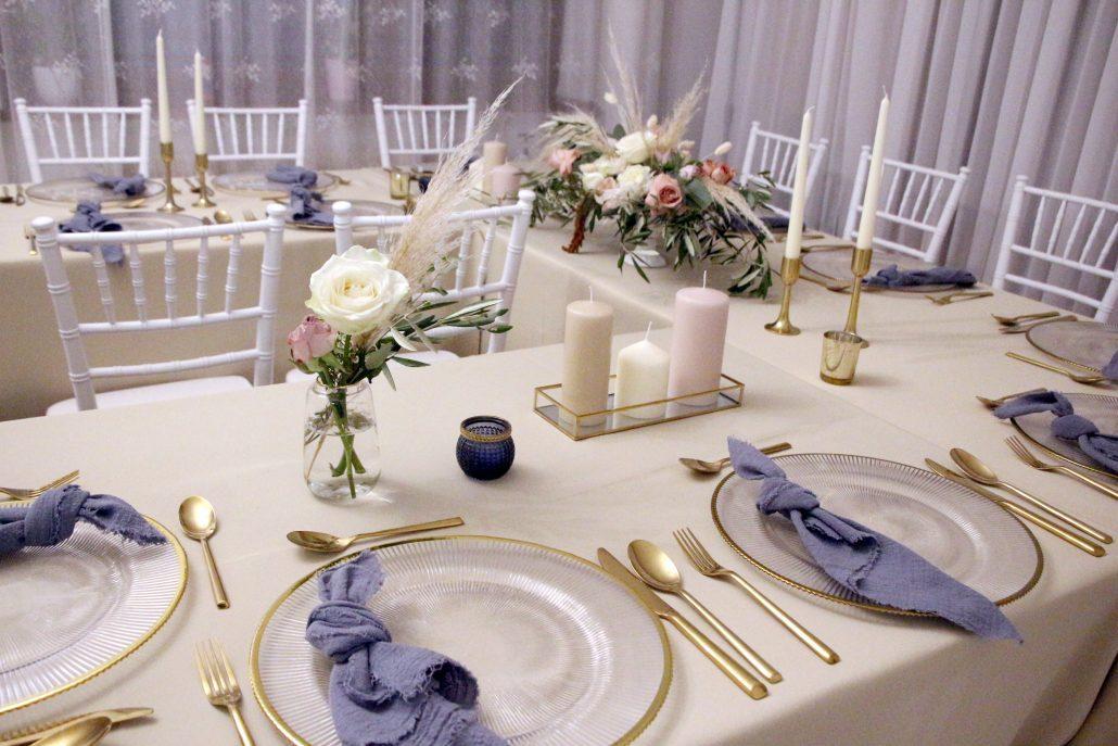Svadobný stôl zdobený v štýle Boho. Klubové taniere, zlatý príbor, soft blue prestieranie a krásna jemná kvetinová výzdoba.