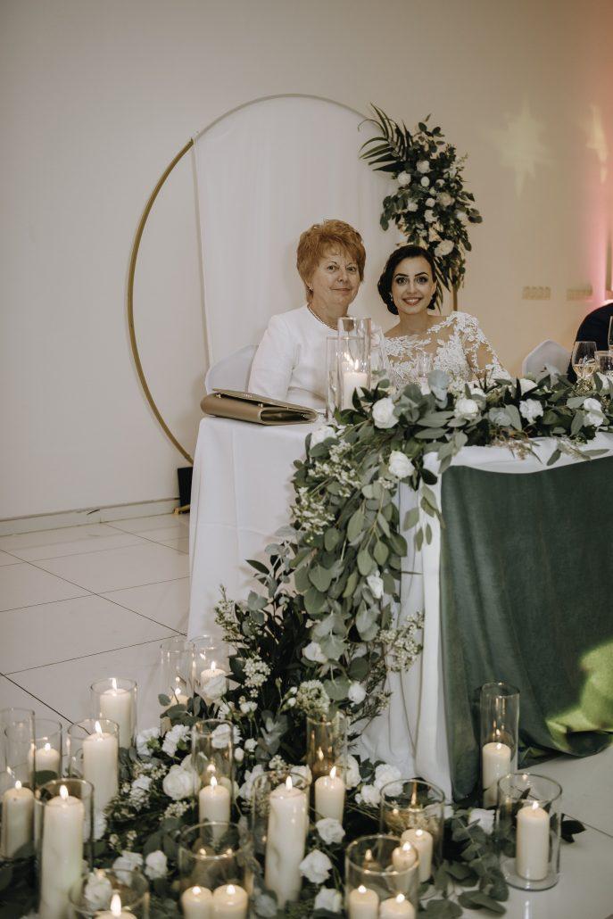 Nevesta so svadobnou mamou sediace pri hlavnom stole, ktorý je nádherne nadekorovaný zeleňou až po zem.