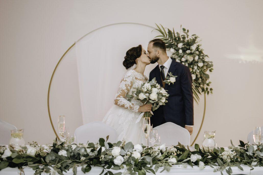 Novomanželia bozkávajúci sa pri hlavnom stole, za hlavným stolom je nadekorovaná krásna kruhová slavobrána od svadobnej agentúry Endless.