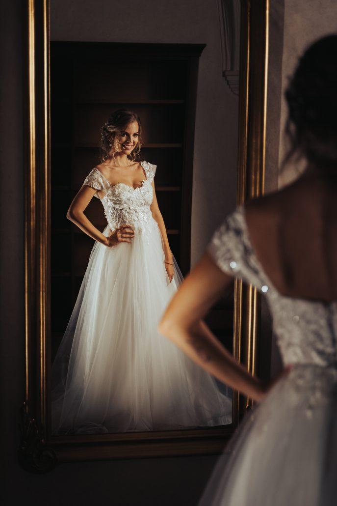 Usmiata nevesty pri pohľade na seba v zrkadle.