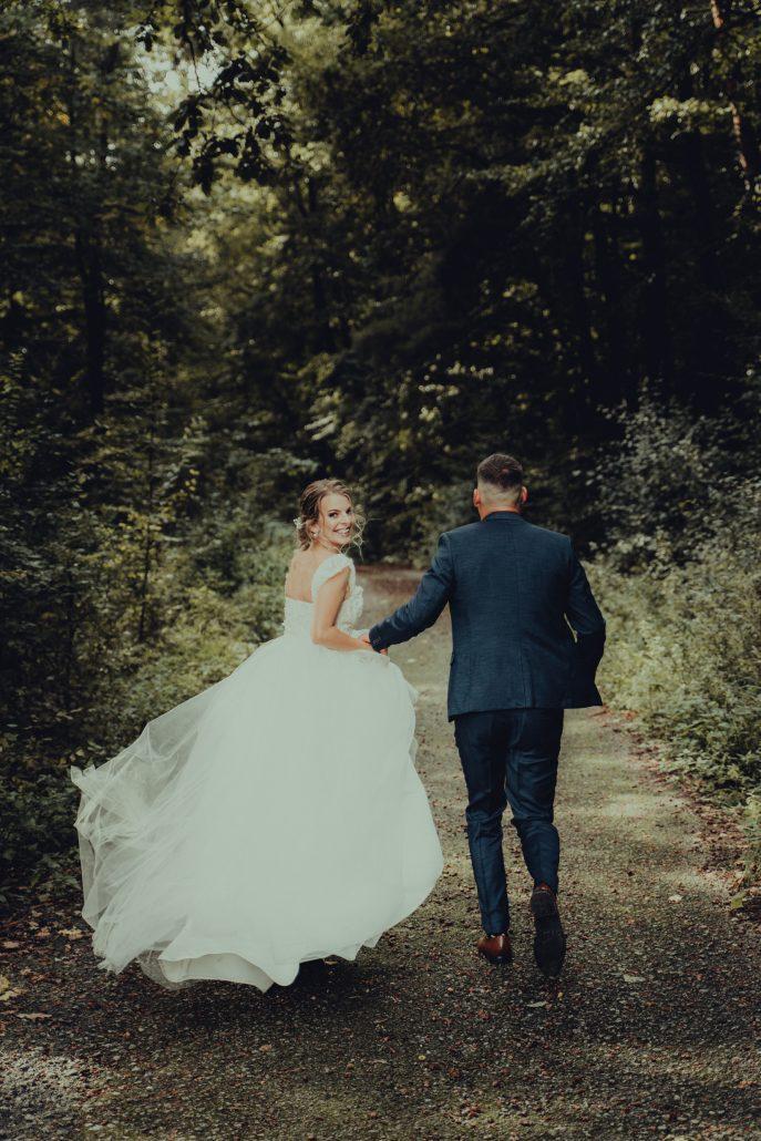 Čerství novomanželia bežia cez les.