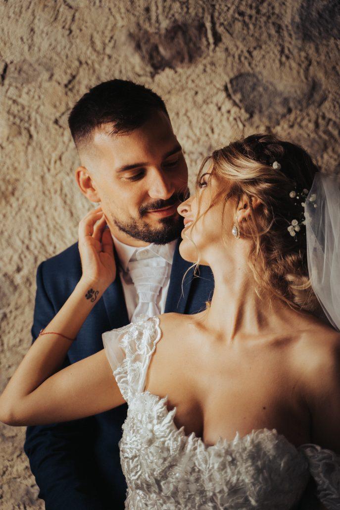 Novomanželia, ktorí sa hladia po tvári.