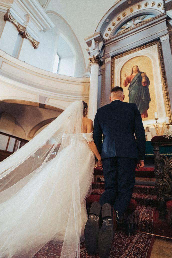 Novomanželia kľačúci na schodoch, ženích má vtipný nápis na podrážke HELP ME, očami Patrik Molčan.
