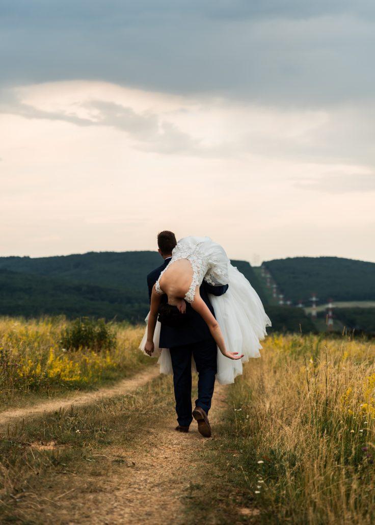 """""""Crazy"""" fotografia, manžel drží svoju nevestu prehodenú cez plece."""