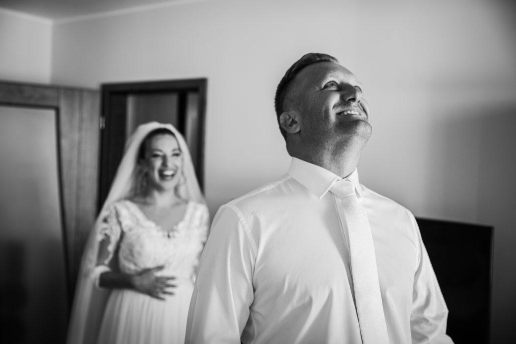 Prvý pohľad novomanželov, žena stojí za ženíchom a čaká, kým sa otočí.
