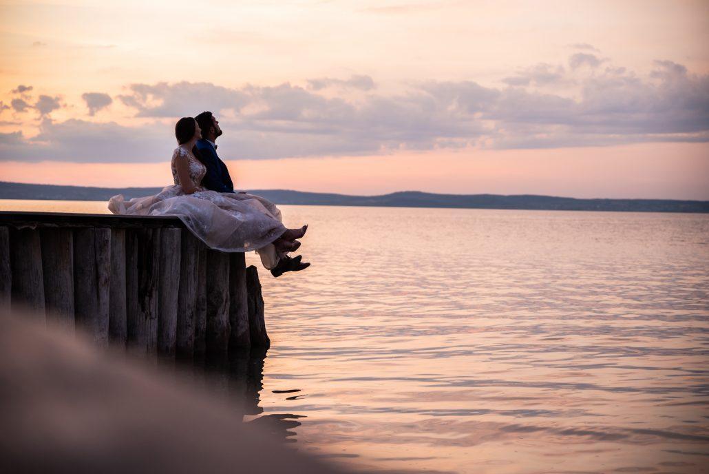 Novomanželia sedia na hrane skaly a užívajú si pohľad na more a hory.