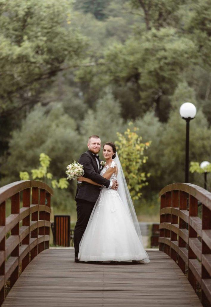 Exteriérová fotografia novomanželov, fotia sa na moste, nevesta má na sebe svadobné šaty, ktoré hviezdili v roku 2020, model Teresa.
