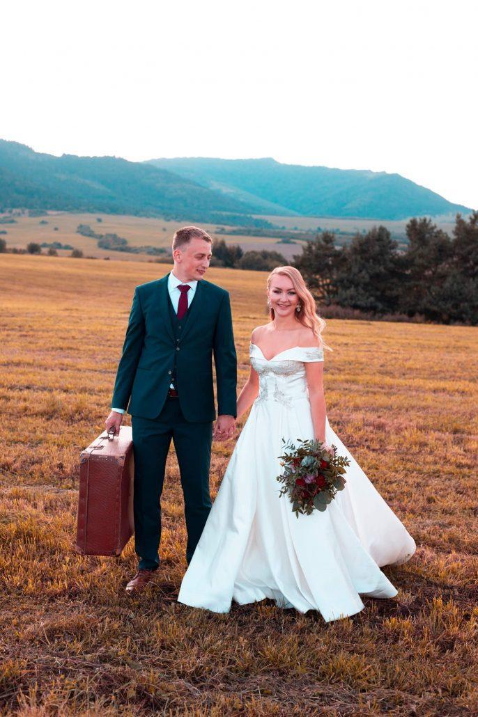 Novomanželia fotení na poli, nevesta má na sebe svadobné šaty, ktoré hviezdili v roku 2020! Značka Eva Lendel, model VOGUE.